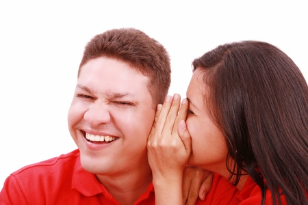 word of mouth: woman telling a man a secret - surprise and fun faces - over a white background Stock Photo