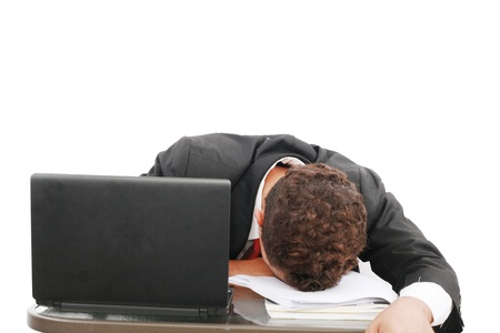 A portrait of a tired businessman resting his head on books over white background