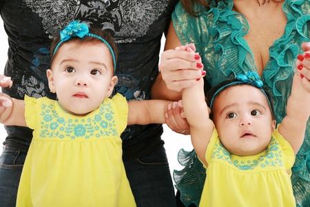 niñas gemelas: Papá y mamá sosteniendo a su hija bebés gemelos Foto de archivo