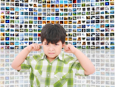 kid protecting ears from loud noise of so many screens talking Stock Photo - 11701339