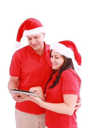 Happy Christmas couple looking a tablet computer. Isolated on white background.  photo