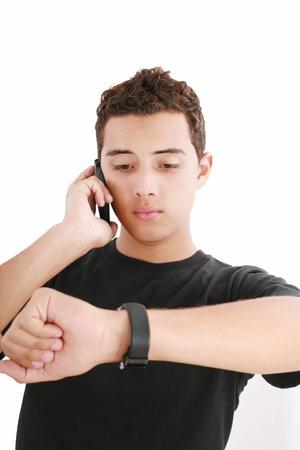punctual: Retrato de un joven ocupado utilizando teléfono móvil y mirando el reloj