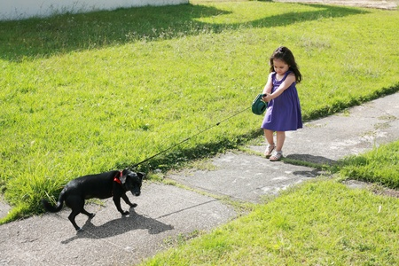 Little girl having trouble with her dog in the park photo