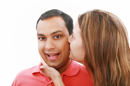 cheek: Young woman kissing her surprised boyfriend, isolated on white Stock Photo