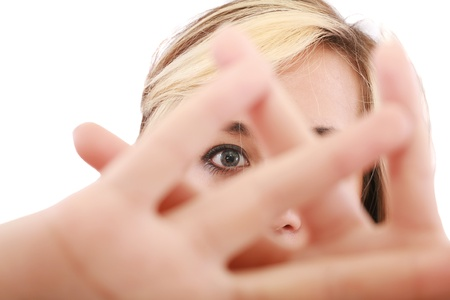 stay beautiful: blonde female hide her face behind her hand, keep away gesture, isolated on white background