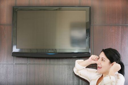 people looking up: Rear view of excited soccer fan standing up and watching favorite team goal at tv