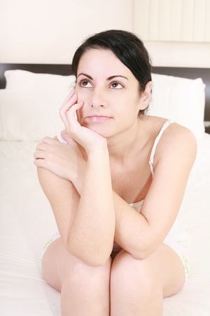 Portrait of an brunette woman in her bedroom photo