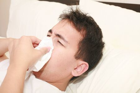 Sick man blowing his nose lying on his bed at morning 