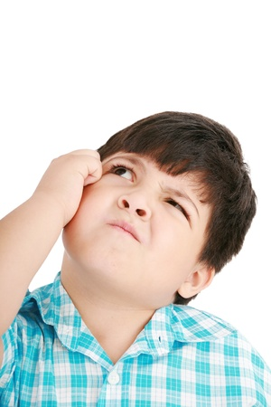 puzzling: boy looking up and scratches his head, isolated on white
