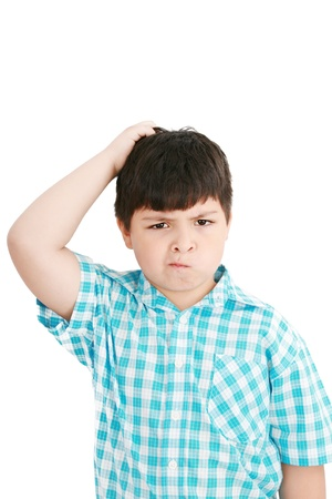 Boy scratches his head in puzzlement or confusion, as if pondering a deep question  Over white background