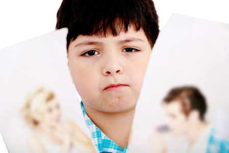 Upset boy standing in front pcture of parents with problems against white background  Stock Photo