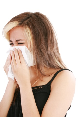 Closeup of gorgeous caucasian woman with cold sneezing into tissue over white background  photo