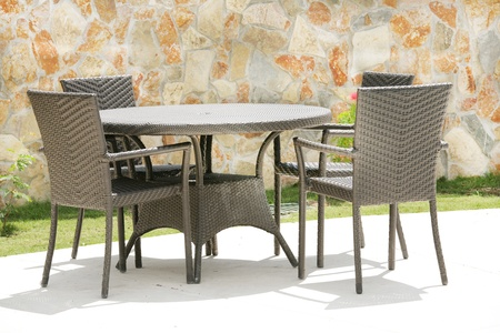 Table and chairs in a tropical garden with a stone wall texture