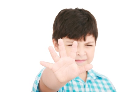 Child looking at camera. Stop signal with his hand.  Boy trying to defend himself isolated on white Stock Photo - 12838359