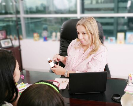A doctor prescribes a medicine to a young patient during visit in the office.  Stock Photo - 12981236