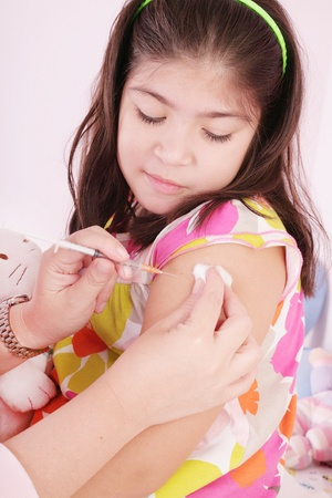 vaccinating: child receiving an injection by the hands of a pediatrician  Stock Photo