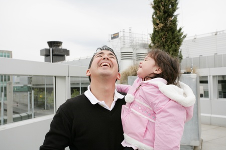 Father and daughter happy looking up outdoors photo