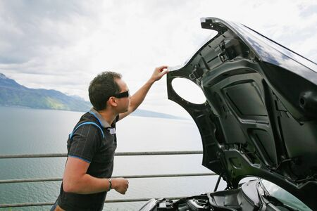 man having a bad day checks his car to figure out what the problem is   photo