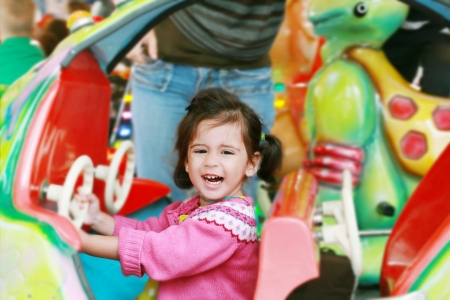 little girl playing on carousel