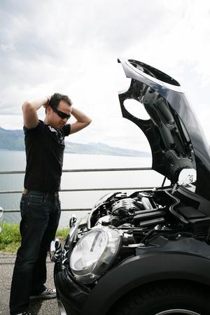 sad man looking at his broken car