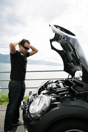 trieste man te kijken naar zijn kapotte auto