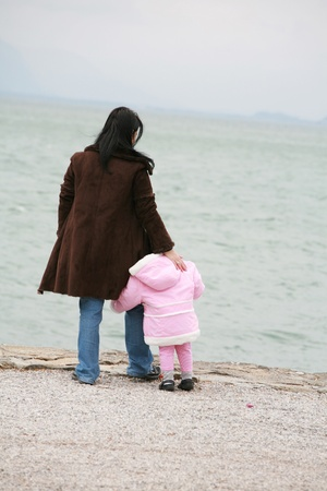 Mother and daughter looking the sea on winter photo