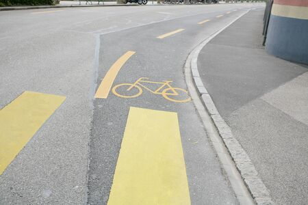 Yellow painted sign for bikes on asphalt  photo