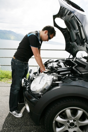 A young man fixing his car up the hills photo