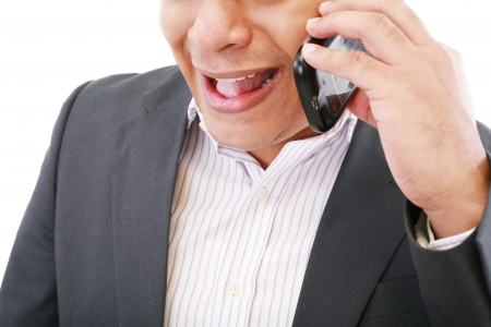 angry young male executive yelling on his mobile phone against white background  photo