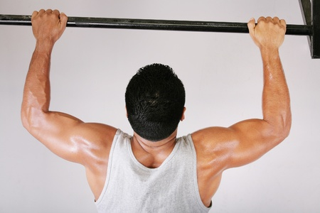 perseverance: Reaching Goal: Strong man doing pull-ups on a bar in a gym Stock Photo
