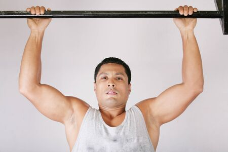 Athlete pull oneself up on gym background  photo