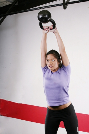 Athletic young woman doing a fitness workout with Kettlebell weights photo