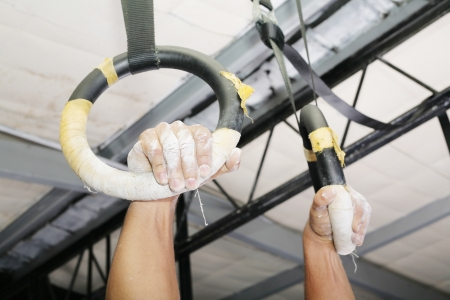 boy gymnast: Human hanging in Gymnastic Rings. Focus on the right hand. Stock Photo