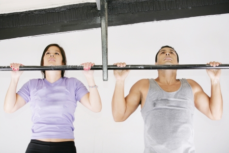 chin: Young adult fitness woman and man preparing to do pull ups in pull up bar.