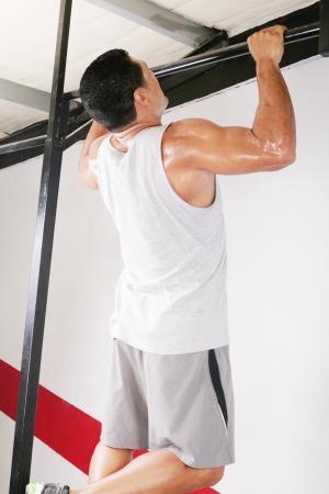 hombre fuerte: hombre fuerte de realizar pull ups en un bar Foto de archivo