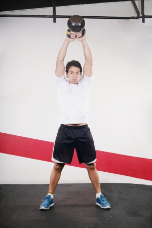 Young man doing kettlebell workout on gym Stock Photo - 15564048