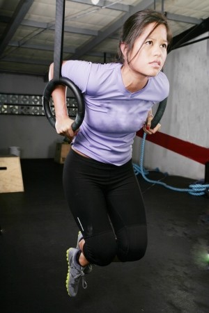 ring up: young woman on rings on gym