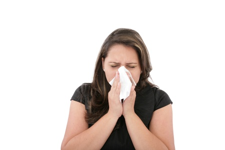 A woman with a cold or allergy wiping or blowing her nose.  photo