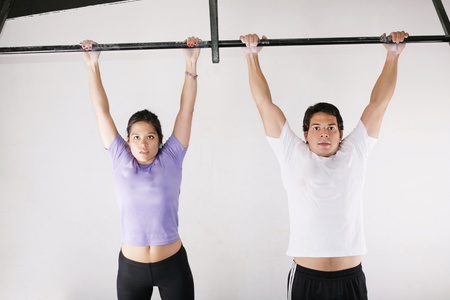 Female and male bodybuilder doing pull-ups on metal bar on gym photo