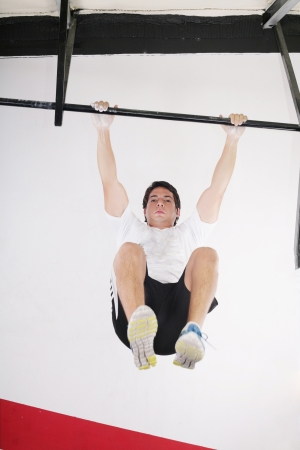fit man performing pull ups in a bar photo