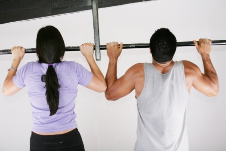 chin: Young adult fitness woman and man preparing to do pull ups in pull up bar