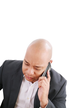 Portrait of a serious businessman talking on mobile phone over white background  photo