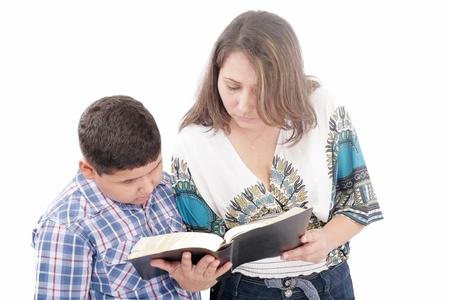 vangelo aperto: Madre e figlio leggendo una Bibbia su uno sfondo nero Archivio Fotografico