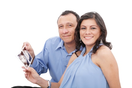 Attractive hispanic young pregnant couple expecting a child holding ultrasound Stock Photo