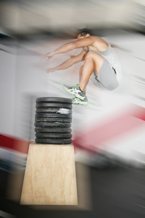Athletic man jumping over a lot of weights
