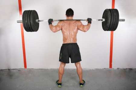 levantamiento de pesas: brazos y la espalda de un hombre joven muscular que se resuelve con una barra