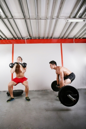 Group of two people exercising using barbells in gym and kettlebell crossfit workout  photo