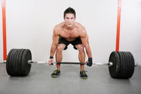 levantar pesas: Chico joven y musculoso sosteniendo una barra. Crossfit ejercicio peso muerto.