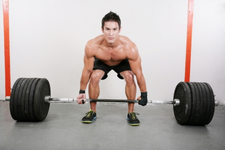 Young and muscular guy holding a barbell. Crossfit dead lift excercise. 