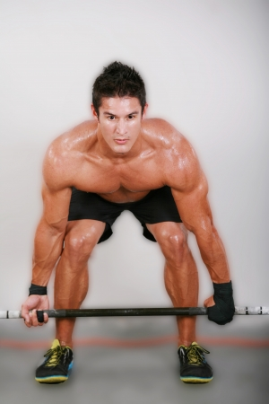 man working out: Young man lifting the barbell in the gym.